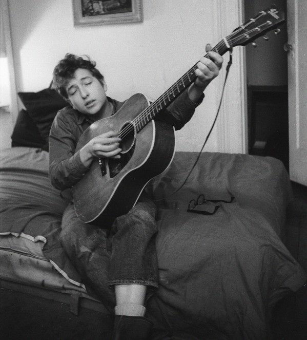 Bob Dylan playing guitar on his bed in his apartment, 161 W 4th St, Greenwich Village, NYC, 1961;© Ted Russell / Govinda Gallery | Bob Dylan, NYC 1961-64 – photographs by Ted Russell | Thursday 21 January  – Sunday 21 February 2016 | Gallery of Photography