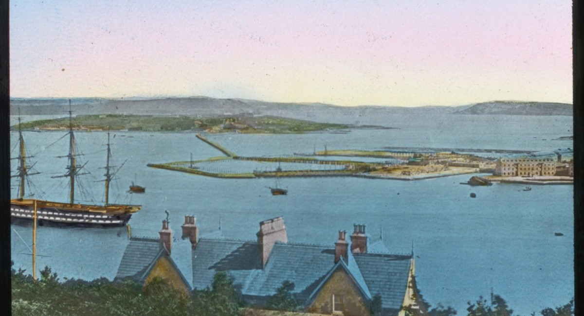 Hand-tinted, late 19th-century lantern slide of Spike and Haulbowline islands and the connecting causeway, completed in 1867 Image © courtesy of Collection of Michael Lenihan. | Spike Island: People and Place 1847 – 1883 | Friday 6 April  – Sunday 1 July 2018 | Sirius Arts Centre