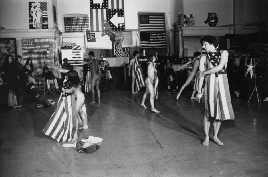 """Peter Moore, Performance view of Yvonne Rainer's """"Trio A with Flag,"""" Judson Memorial Church, 1970. © Barbara Moore/Licensed by VAGA, New York, NY. Courtesy Paula Cooper Gallery, New York. 