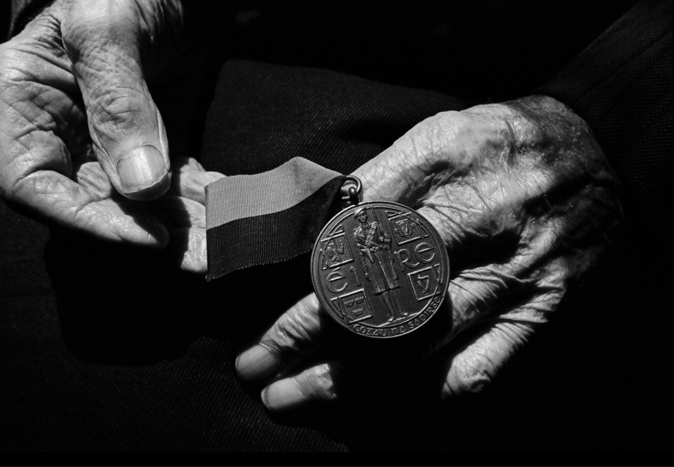 Seamus Murphy: The hands of Batt Moriarty at home in County Cork holding his 'Black and Tan' medal awarded to IRA men who fought in Ireland's War of Independence with Britain. Batt Moriarty -Cork No. 4 Brigade. Intelligence Officer. IRA 1918-1923. | Seamus Murphy: Citizens | Friday 20 November 2020  – Friday 26 February 2021 | Source Arts Centre